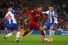 Liverpool's Roberto Firmino in action with Porto's Soares and Otavio.