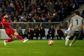 Mohamed Salah scoring Liverpool's second goal past Iker Casillas.