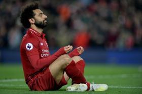 Mohamed Salah celebrates with a meditation pose after scoring against Huddersfield.