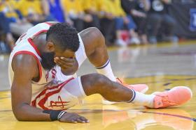 James Harden falls to the floor grabbing his face after being accidentally poked in the eye by Golden State Warriors' Draymond Green.
