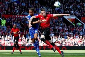 Manchester United's Phil Jones challenging for the ball with Cardiff City's Bobby Reid.