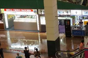 An afternoon downpour flooded shops in People's Park Complex in Chinatown yesterday. Shopkeepers said rainwater started flooding the carpark at about 1.20pm, before entering the first three storeys of the complex. Ms Emerald Tang, 33, said many of her perfume products, including luxury brands such as Chanel and Dior, were damaged.