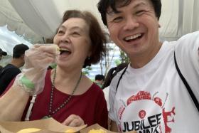 The writer taking a selfie with his mother eating durian.