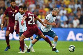 Argentina's Sergio Aguero surging past Venezuela's Ronald Hernandez.