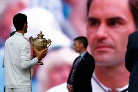Novak Djokovic (left) holding the Wimbledon trophy after defeating Roger Federer (right).