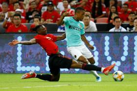Manchester United right-back Aaron Wan-Bissaka tackling Inter Milan's Estevao Dalbert.