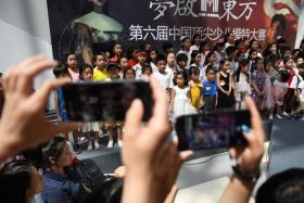 Parents taking photos of their children before a child model contest in Beijing