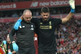 Liverpool goalkeeper Alisson (right) receiving medical treatment for a calf injury.