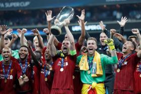 Liverpool captain Jordan Henderson lifting the European Super Cup.