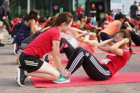Participants at the sit-up station of the GE Women's Individual Physical Proficiency Test (IPPT).