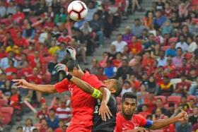 Singapore's Safuwan Baharudin (left) and Hariss Harun challenge Yemen goalkeeper Salem Abdullah for a high ball during a World Cup 2022 qualifier.