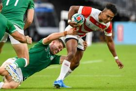 Japan's Kotaro Matsushima (right) is tackled by Ireland's wing Jacob Stockdale.
