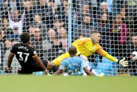 Adama Traore scoring Wolves' second goal past Manchester City goalkeeper Ederson.