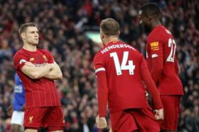 James Milner (left) celebrates with Jordan Henderson and Divock Origi after scoring the late penalty winner.