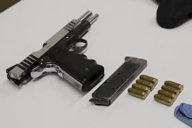 Two men charged over pistol, bullets found in CNB raid