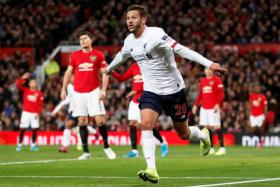 Adam Lallana celebrates after scoring Liverpool's equaliser.