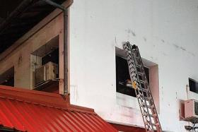 Men escape smoke-filled shop house unit through window