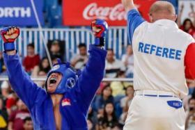 Singapore's Nazri Sutari (in blue) celebrates after defeating Indonesia's Jason Sim.
