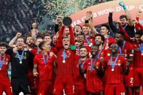 Liverpool skipper Jordan Henderson lifting the club's third trophy this year.