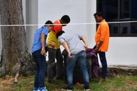 Police officers and cleaners checking the contents of the bin at the bottom of a rubbish chute at Block 534 Bedok North Street 3 on Jan 7, 2020.