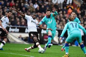 Valencia midfielder Geoffrey Kondogbia (left) challenging Barcelona's superstar Lionel Messi.