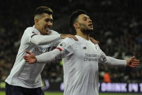 Liverpool's Roberto Firmino (left) celebrating with Alex Oxlade-Chamberlain after the Englishman made it 2-0.