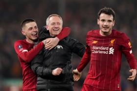 Liverpool Under-23 manager Neil Critchley celebrating with his players after reaching the FA Cup fifth round.