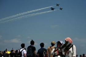 A crowd watching a display at the Singapore Airshow 2018.