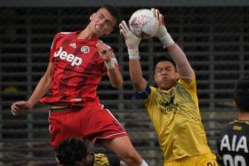 Tampines Rovers goalkeeper Syazwan Buhari (right) claiming the ball as Balestier Khalsa's Ensar Bruncevic challenges.