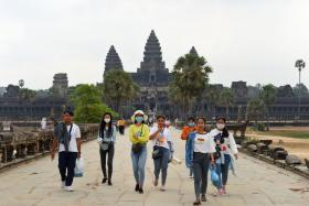 People wear facemasks, amid concerns about the spread of the COVID-19 novel coronavirus, as they visit the Angkor Wat temple in Siem Reap province on March 6, 2020. - The deadly COVID-19 novel coronavirus epidemic will cost world tourism at least $22 billion owing to a drop in spending by Chinese tourists, the head of the World Travel and Tourism Council said on February 27.