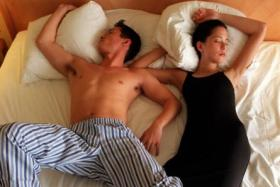Posed photo of a couple sleeping together on a bed. For some six hours is enough, for others, 10. It's fine so long as one can perform well in the day. But most would not go wrong with seven to eight hours of sleep.