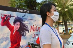 "A woman, wearing a facemask amid concerns about the spread of the COVID-19 novel coronavirus, waits to cross the street in front of a poster for the Disney film ""Mulan"" in Vientiane on March 11, 2020."