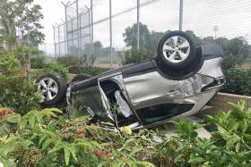 Car flips over after crashing into road divider, two taken to hospital