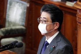 Wearing a mask, Mr Shinzo Abe speaks during a lower house plenary session in Tokyo's parliament.