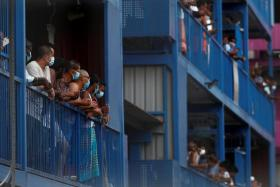 Workers from Bangladesh, India and China look out of their balconies during food distribution at Punggol S-11 workers' dormitory, which was gazetted to be an isolation facility after it became a cluster of coronavirus disease (COVID-19) cases, in Singapore