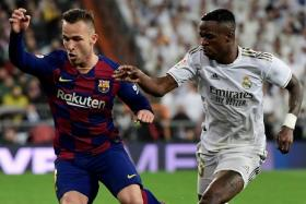Barcelona midfielder Arthur Melo (left) couldn't stop Vinicius Junior's Real Madrid from winning 2-0 in El Clasico last month.