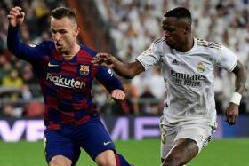 Barcelona midfielder Arthur Melo (left) couldn't stop Vinicius Junior's Real Madrid from winning 2-0 in El Clasico last month.