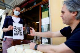 A waiter holds a placard showing a barcode that customers scan on their phones to view the restaurant menu, to avoid using paper menus that are touched by many customers, as Italy eases some of the lockdown measures put in place following the coronavirus disease (COVID-19) outbreak, in Rome, Italy, May 20, 2020.