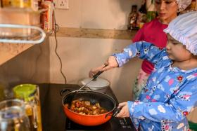 This photo taken on May 21, 2020 shows Moe Myint May Thu (R) and her mother Honey Cho cooking while filming a video at their house in Yangon. - From boiled catfish soup to spicy fried frog, an eight-year-old in pyjamas and a chef's hat is delighting Myanmar with her culinary prowess in online classes to a nation still told to stay at home due to the coronavirus pandemic.