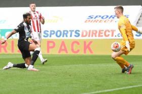 Newcastle United striker Joelinton scoring against Sheffield United goalkeeper Dean Henderson. The goal is Joelinton's first in the English Premier League since August.