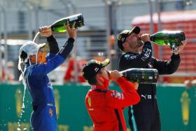 (From right) Valtteri Bottas, Charles Leclerc and Lando Norris celebrating with champagne after the race.