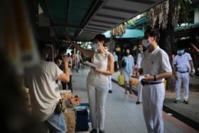 Josephine Teo and Heng Chee How interact with the residents during a walkabout at Whampoa Market on July 5.