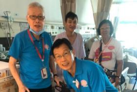 Stroke survivor Mr Michael Yap (left) and his wife (right) volunteer at Yishun Community Hospital, sharing his stroke experiences with them.