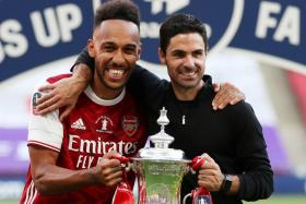 Arsenal striker Pierre-Emerick Aubameyang (left) posing with manager Mikel Arteta, after the Gunners won their 14th FA Cup trophy last season.