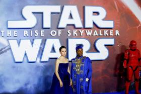 """Cast members Daisy Ridley and John Boyega pose as they attend the premiere of """"Star Wars: The Rise of Skywalker"""" in London, Britain, December 18, 2019."""