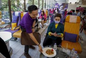A Thai Airways staff member brings food to a woman seated on an airplane seat at the newly opened Thai Airways inflight-themed restaurant at the company's headquarters in Bangkok, Thailand, 04 September 2020.