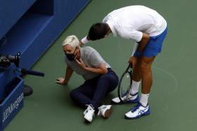 Novak Djokovic trying to help a linesperson after hitting her with a ball on the throat during his match against Pablo Carreno Busta of Spain.