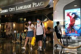 "People walk near an advertisement for Disney's film ""Mulan"" at a cinema in Hong Kong, China September 8, 2020."
