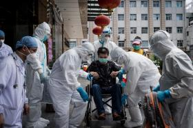 This photo taken on June 17, 2020 shows medical workers carrying a man who is the last patient recovered from the COVID-19 coronavirus infection in the Wuhan, pulmonary hospital before he leaves the hospital in Wuhan, in China's central Hubei province.