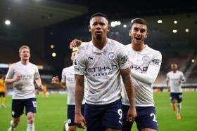 Striker Gabriel Jesus (centre) celebrates with Ferran Torres after scoring Manchester City's third goal against Wolverhampton Wanderers in stoppage time.